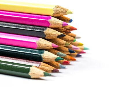 Colored pencils for drawing and learning at school lie on a white background