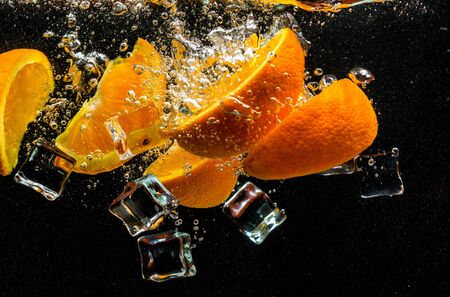 Oranges and ice fall into the water with splashes on a black background.