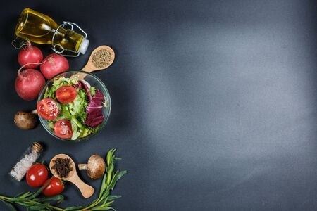 Vegetables for diet, different spices on a black background Stockfoto