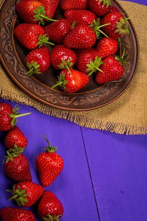 Ripe red strawberries on a purple wooden background Standard-Bild