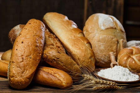 Fresh assorted loaves of gluten-free bread on wooden table Archivio Fotografico