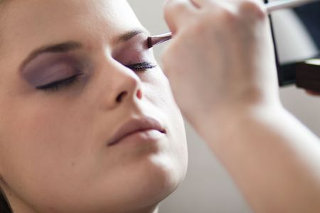 Make-up artist applays purpple color on eye lids with brush photo