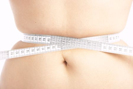Woman measuring her belly with tame measure photo
