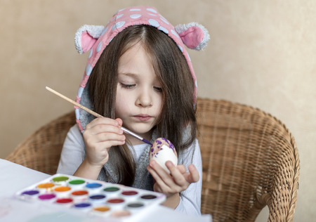 Little cheerful active child girl long hair and rabbit ears paints an egg with pink paint on Easter. Spring traditions