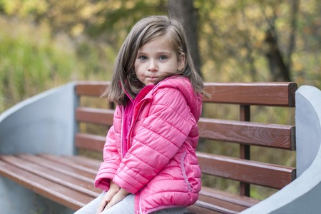 Little pretty girl in a pink coat sitting on a wood bench at the park in autumn. Emotional portrait. Childhood concept. Caucasian. Child with brunette long hair. Leisure, relaxation, lifestyle