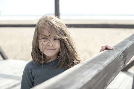 Vacation by the sea. Cute kid on the deserted beach. Summer, outdoors. Wind in the hair. Little smiling sweet baby girl. Beach landscape. On the blurred background of the wood railing and the sea Foto de archivo