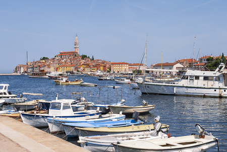 Old center harbor with fishing boats during a summer day. Wonderful romantic bright view of the medieval Rovinj, Croatia, Istria.  A picturesque town with colorful houses and characteristic church