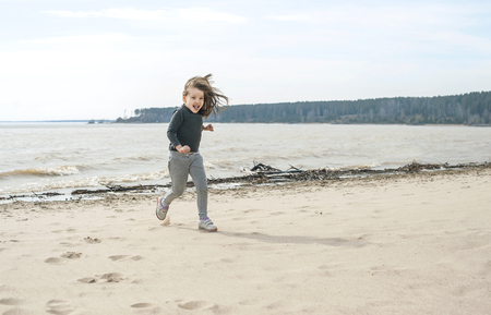 Little sweet girl with brown long hair running on the beach on a cloudy day. Vacation by the sea. Cute kid girl on the deserted beach. Summer, outdoors. Wind in the hair girl. Beach landscape Standard-Bild