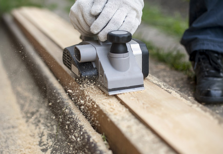 Carpenter working with electric planer on wooden plank in outdoor. Woodworking and craftsmanship concept