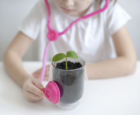 Little girl imagining herself as doctor while playing with pink stethoscope. Young plants. Caring for a new life. Climate change. Stop global warming. Earth Day holiday concept. World Environment Day