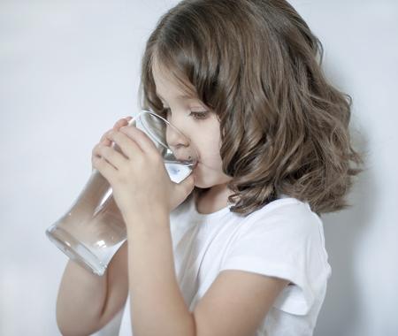 Kind dat thuis schoon water drinkt, close-up. Klein schattig meisje met waterglas in haar hand. Zorgen voor eigen gezondheid. Concept van gezonde levensstijl, goede gewoonte