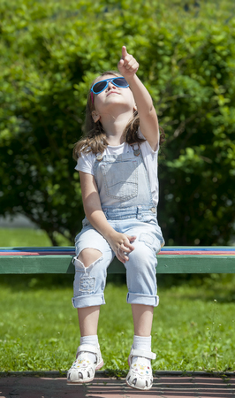Little beautiful girl in sunglasses is sitting on the wooden park bench and pointing her finger at the sky. The wind blows her hairy. Juicy green background. Child looks dreamy and fashion concept