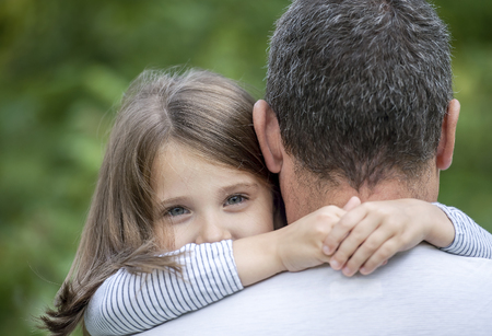Portrait of cute little girl held in fathers arms. Happy loving family. Father and his daughter child girl playing hugging. Cute baby and daddy. Concept of Father day. Family holiday and togetherness