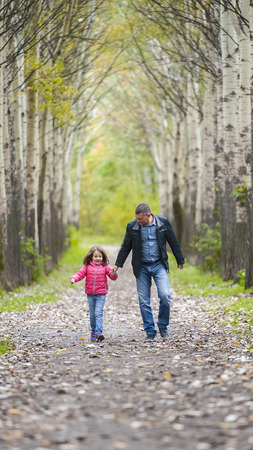 The father runs with a daughter and holds her hand on nature on autumn day vacation. Dad and girl walking and playing in the park. Concept of friendly family. Happiness and going home