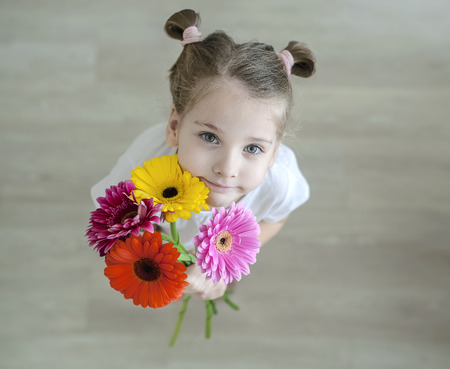 Adorable little girl with cute smile and face expression holding bouquet of pink, purple, yellow, orange gerbera daisies. Happy Mothers Day, Womens day, Fathers day or Birthday background. Top view