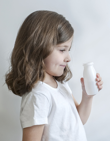 Smiling young girl showing plastic white bottle. Cute baby is drinking for milk or yogurt. Portrait view profile. Kid keeping white small vial in her hands