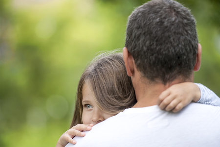 Girl hugging her father. Happy loving family. Dad and his daughter playing. Cute baby and daddy. Concept of Father day. Family holiday and togetherness. Green background Reklamní fotografie