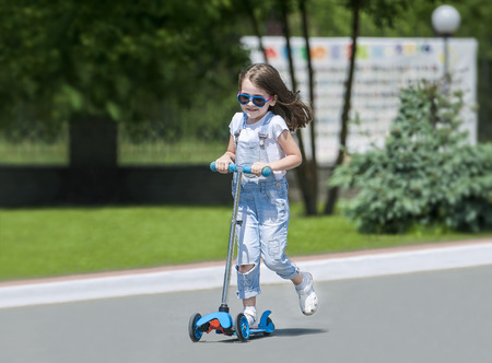Child riding scooter. Kid on colorful kick board. Active outdoor fun for kids. Summer sports for preschool children. Little happy girl in spring park. The concept of a healthy lifestyle Reklamní fotografie