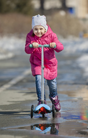 Child riding scooter. Kid on colorful kick board. Active outdoor fun for kids. Sports for preschool children. Little happy girl in spring park. The concept of a healthy lifestyle Archivio Fotografico