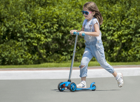 Child riding scooter. Kid on colorful kick board. Active outdoor fun for kids. Summer sports for preschool children. Little happy girl in spring park. The concept of a healthy lifestyle