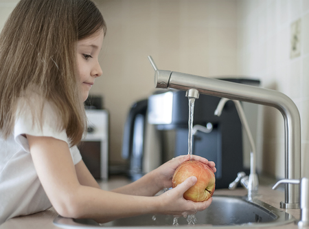A cute little girl washes a red yellow apple in a sink. Child is washing the fruit in kitchen. Little child learns the rules of hygiene. Child uses the tap himself. Healthy lifestyle hygiene concept Reklamní fotografie