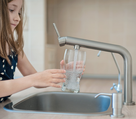 Portrait of a little caucasian girl gaining a glass of tap clean water. Kitchen faucet. Cute curly kid pouring fresh water from filter tap. Indoors. Healthy life concept Reklamní fotografie