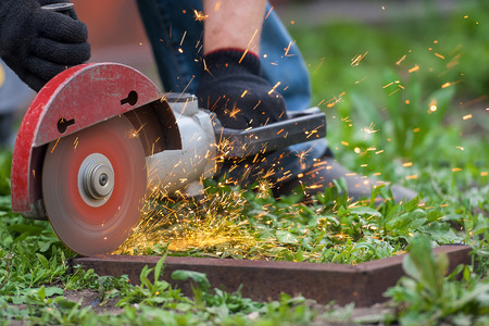 Worker outside, cut the metal rails using angle grinders Stock Photo