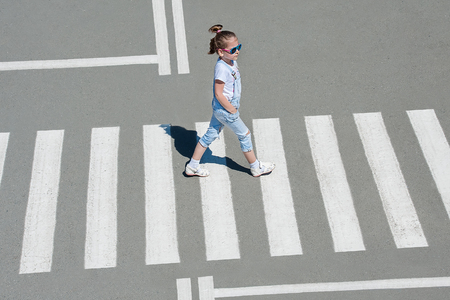 In the summer on the street at the pedestrian crossing kid girl in fashion clothes cross the road. From top view. Shadow at zebra crossing