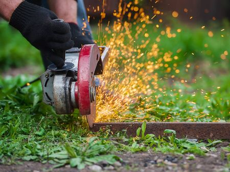Hand of man with steel cutter tool on green background. Worker outside, cut the metal rails. Process with angle grinder. Electrical saw generating hot sparks. Construction concept