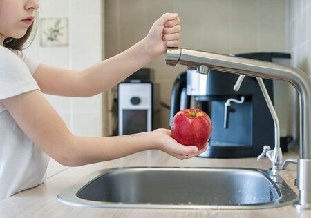 A cute little girl washes a red yellow apple in a sink. Child is washing the fruit in kitchen. Little child learns the rules of hygiene. Child uses the tap himself. Healthy lifestyle hygiene concept 版權商用圖片