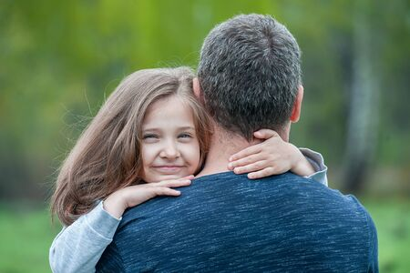 Portrait of cute little girl held in father's arms. Happy loving family. Father and his daughter child girl playing hugging. Concept of Father day. Family holiday and togetherness 版權商用圖片