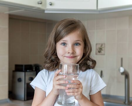 Little child is drinking clean water at home, close up. Caucasian cute girl with long hair is holding a water glass in her hands. Taking care of own health. Concept of healthy lifestyle, good habit 版權商用圖片