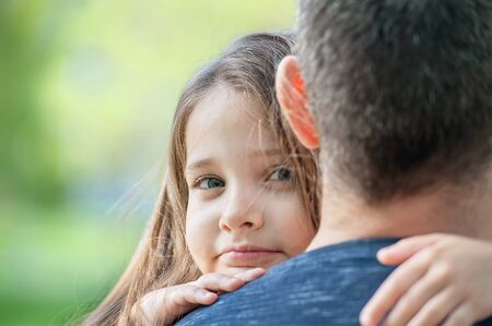 Portrait of cute little girl held in father's arms. Happy loving family. Father and his daughter child girl playing hugging Concept of Father day. Family holiday and togetherness 版權商用圖片