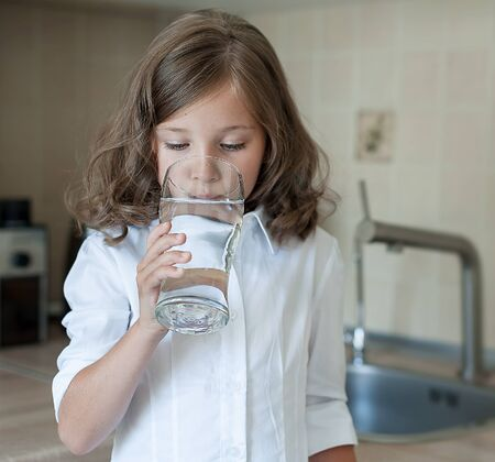 Portrait of a little caucasian baby girl holding a glass of tap clean water. Kitchen faucet. Cute kid pouring fresh water from filter tap. Indoors. Healthy life concept