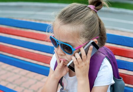 Young caucasian girl with a sad face holding mobile phone, making a call, talking on the phone, sitting on bench at park in summer. Portrait of child using smart phone outdoor. Communication concept 版權商用圖片