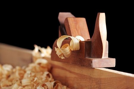 whittle: shaving and wooden plane on a black background Stock Photo