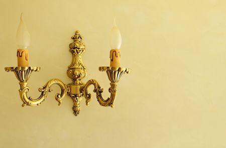 wall sconce: candelero de bronce en una pared de color amarilla