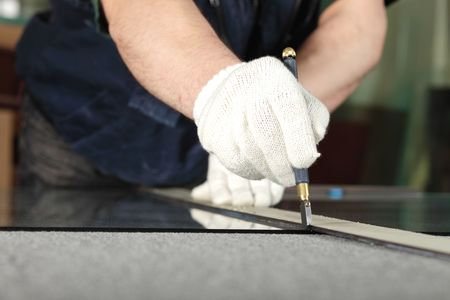 The worker, cutting a mirror,focus on a hand photo