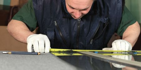 The worker, cutting a glass,focus on a hands photo