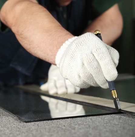 The worker, cutting a mirror,focus on a hand with tool photo