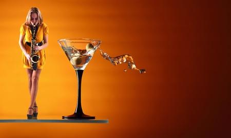 copa martini: Martini y mujer con vestido amarillo con el saxofón.  Foto de archivo