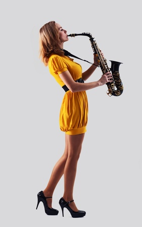 woman with saxophone on a grey background. photo