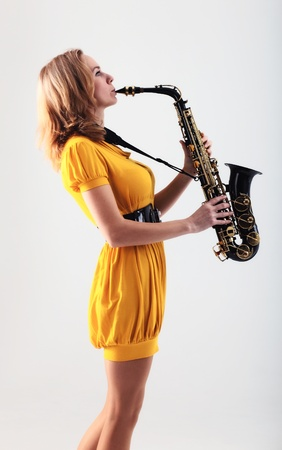 young woman in yellow dress with saxophone.