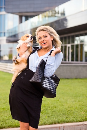 happy blond woman with chihuahua in downtown. photo
