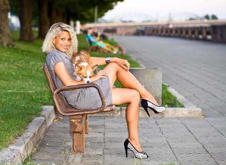 pretty blonde girl: happy blond woman with chihuahua on a bench in park.