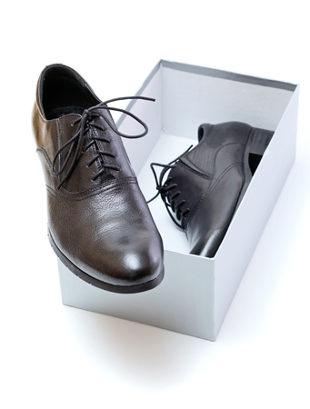 New black shoes with laces and grey box on a white background. photo