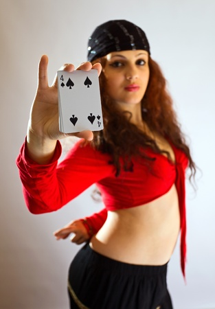 The young beautiful gipsy girl predicts the future on cards.Focus on a card. Stock Photo - 10943788