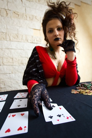 tell fortune: The young beautiful gipsy girl predicts the future on cards.Focus on a foreground. Stock Photo