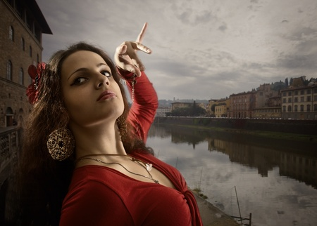 italian culture: The young woman in  red dress dances on the bank of the river. Italy, Florence.