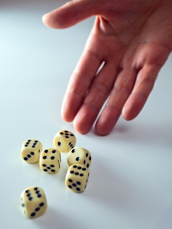 risking: The hand of the person throwing cubes for dicing. Stock Photo